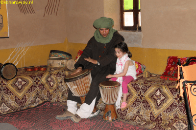 Kind en Berber spelen op traditionele drums in Marokko